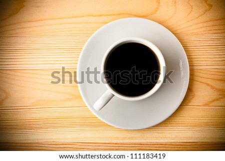 Fresh Black Coffee in a White Ceramic Cup on a Saucer on a Wooden Table