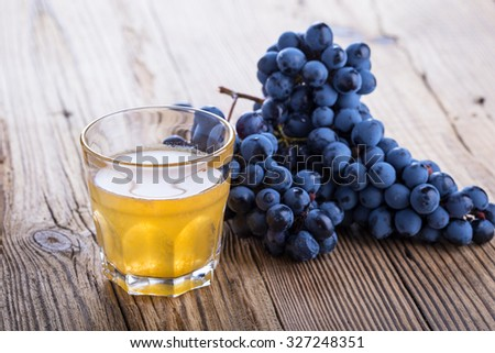 Fresh black grapes and freshly squeezed grape juice on rustic wooden table, harvest time, selective focus - stock photo