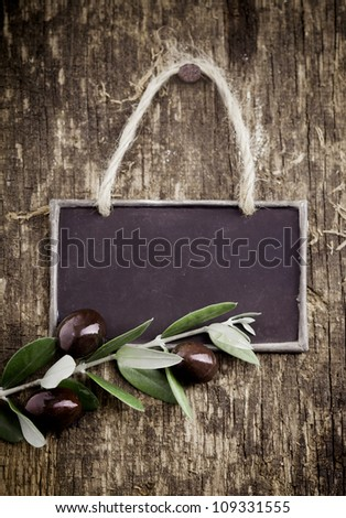 Fresh black olives lying with a slate blackboard on an old grungy weathered and textured wooden table - stock photo