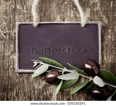 Fresh black olives on a leafy twig and a blank slate for your text lying on an old weathered wooden table - stock photo