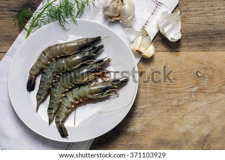 fresh black tiger shrimps on a white plate ready for preparation on a rustic wooden board, garlic and dill garnish, view from above, copy space - stock photo