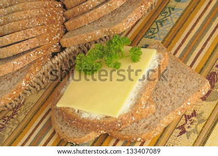 Fresh black whole grain bread with butter cheese and parsley