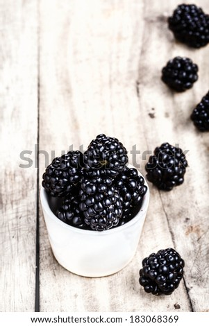 Fresh Blackberries in a white bowl on  wooden background close up with copyspace in Rustic style. - stock photo