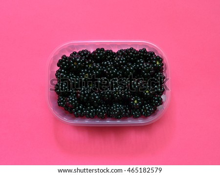 Fresh blackberries in plastic box on a pink background