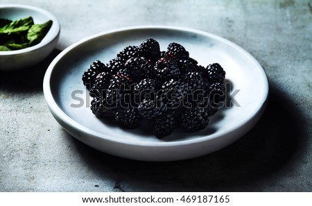 Fresh Blackberry on white plate on the ground