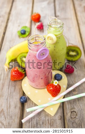 Fresh blended fruit smoothies in vintage milk bottles with berries on rustic wooden table - stock photo