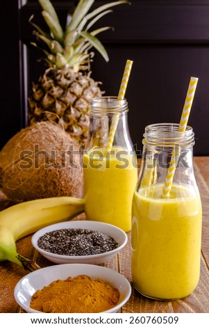 Fresh blended fruit smoothies made with pineapple, banana, coconut, turmeric and chia seeds surrounded by raw ingredients in glass milk bottles with yellow straws - stock photo
