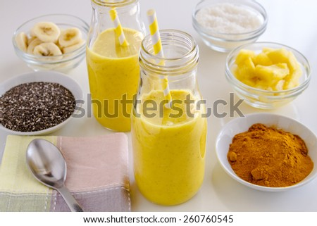 Fresh blended fruit smoothies made with pineapple, banana, coconut, turmeric and chia seeds surrounded by raw ingredients yellow straws - stock photo