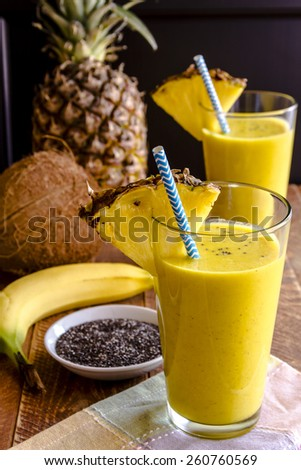 Fresh blended fruit smoothies made with pineapple, banana, coconut, turmeric and chia seeds surrounded by raw ingredients in drinking glass with pineapple slice garnish and blue striped straw - stock photo