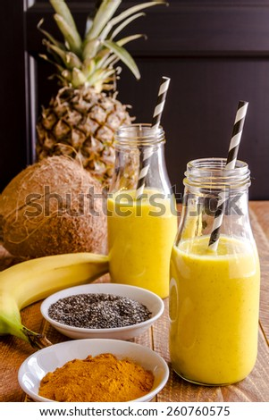 Fresh blended fruit smoothies made with pineapple, banana, coconut, turmeric and chia seeds surrounded by raw ingredients in glass milk bottles with black and white straws - stock photo