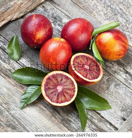 Fresh blood oranges on wooden background - stock photo