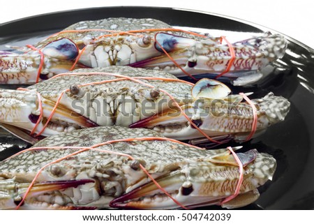 Fresh blue crab in black dish for cooking.
