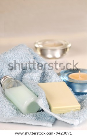 Fresh blue towels with shampoo, soap and candles - stock photo