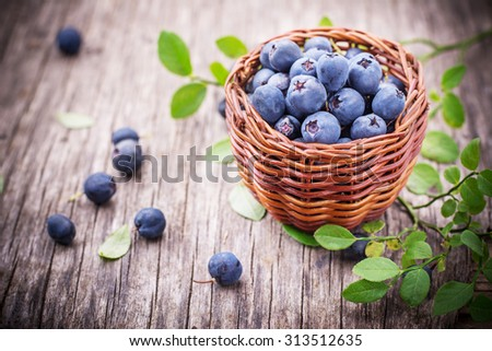 fresh blueberries in a little basket on a table. Selective focus - stock photo