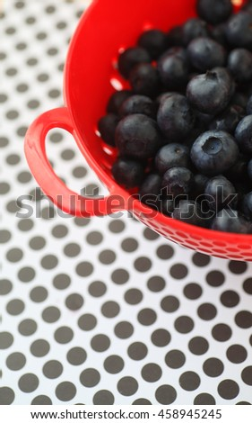 Fresh blueberries in a red colander on black and white polka dots