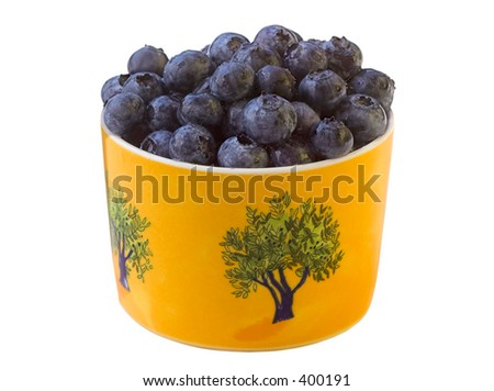 Fresh Blueberries in a Yellow Desert Cup. What you see on the cup surface is not grain; it's the texture of the cup and glaze. - stock photo