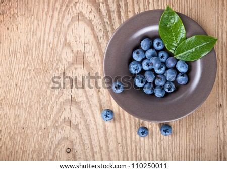 Fresh blueberries in bowl with leaves on wooden background with copy space. Top view - stock photo