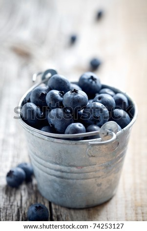 Fresh blueberries in small bucket, selective focus - stock photo