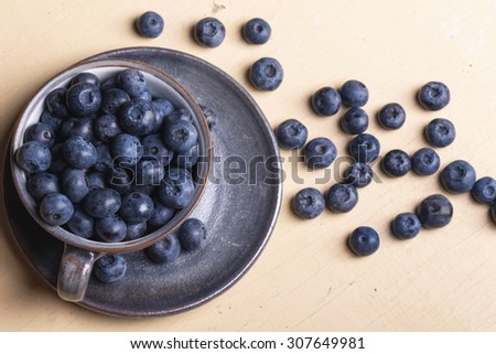 Fresh blueberries in the vintage  blue cup on a rustic creamy wooden board