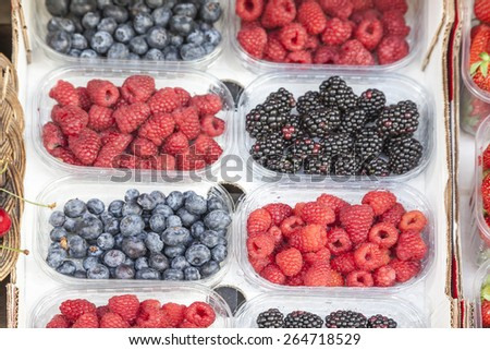 Fresh blueberries, raspberries and blackberries on a market in Italy - stock photo