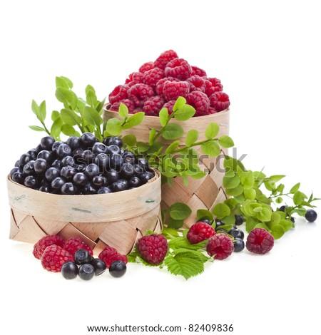 fresh blueberries , raspberries in the basket on white - stock photo