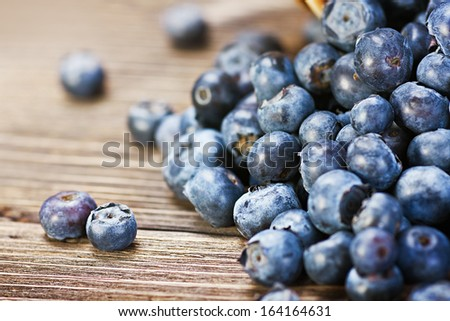 Fresh blueberries scattered on the wooden table. Shallow depth of field, focus on left berry.