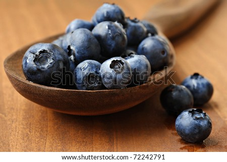 Fresh blueberries spilling from vintage wooden spoon onto wood table.  Macro with extremely shallow dof. - stock photo