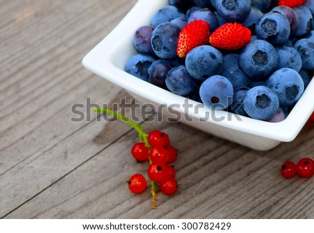Fresh blueberries, strawberries and currants in white bowl on wooden table. - stock photo