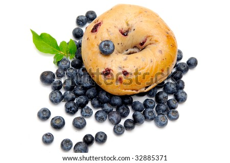 Fresh blueberries surround a single blueberry bagel on a light background - stock photo