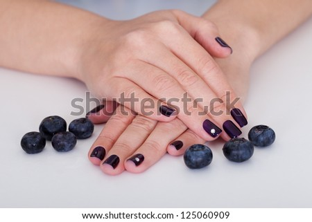 Fresh blueberries  surrounding the hand of a woman with beautiful purple nails - stock photo