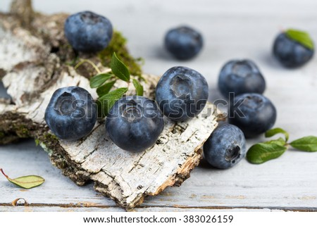 Fresh blueberries with leaves on birch bark, closeup - stock photo