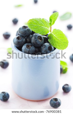 Fresh blueberry in a cup  with leaves of mint - stock photo