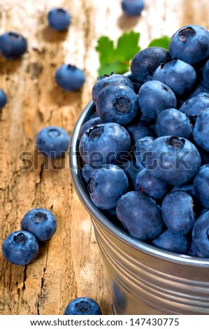 Fresh blueberry in a metal bucket on a wooden background - stock photo