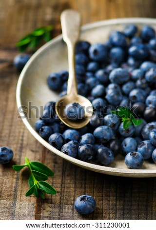 fresh blueberry in to the vintage metall plate . style vintage. selective focus.