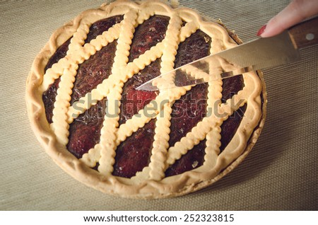 fresh blueberry pie is cut with a knife