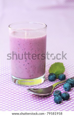 Fresh blueberry smoothie with fresh fruits on a lilac background - stock photo