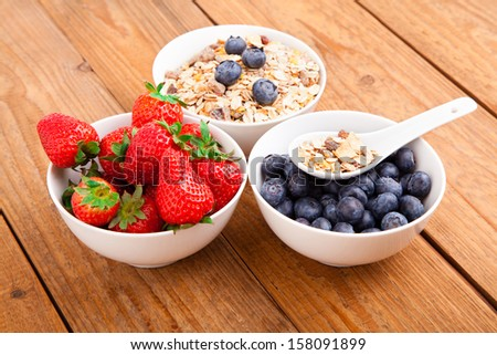 fresh blueberry, strawberry and corn flakes in white porcelain bowl, wooden table - stock photo