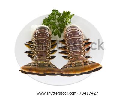 Fresh Brazilian tails, parsley on white dinner plate - stock photo
