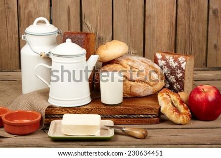 Fresh bread and butter and milk on wooden background - stock photo
