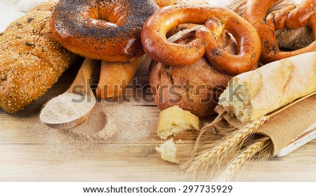 Fresh bread and flour on a rustic wooden table.