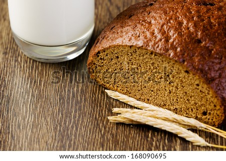 Fresh bread and glass of milk on table