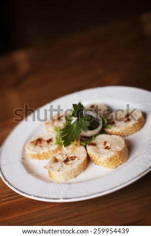 Fresh bread and homemade butter with red hot chilly pepper on wooden background. - stock photo