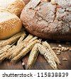fresh bread and rolls with ears of wheat on the table - stock photo