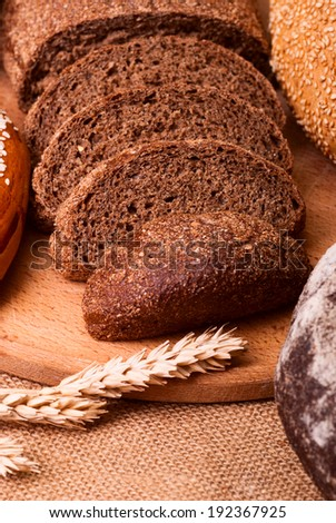 fresh bread and wheat on the burlap - stock photo