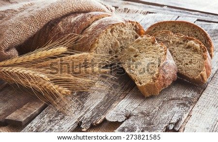 Fresh bread and wheat on the old wooden background. Toned - stock photo