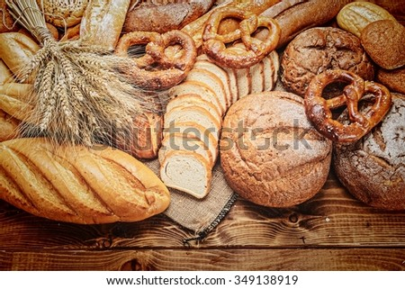 fresh bread  and wheat on the wooden board - stock photo