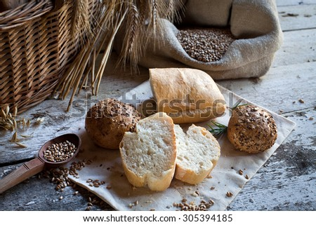 fresh bread and wheat on the wooden table - stock photo