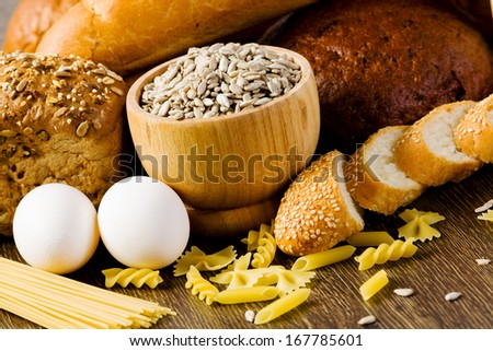 Fresh bread, eggs and macaroni on table