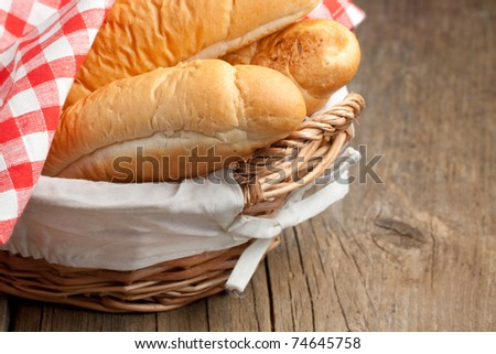 Fresh bread in basket on old wooden table - stock photo