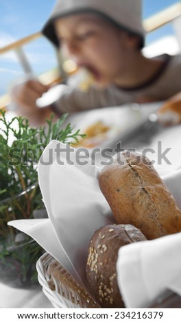 Fresh bread in front of an eating blurred in the background boy. - stock photo